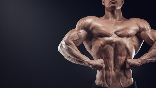 Bel culturista muscoloso in posa sul davanti lat spread display larghezza lat dalla parte anteriore del torace thic...
