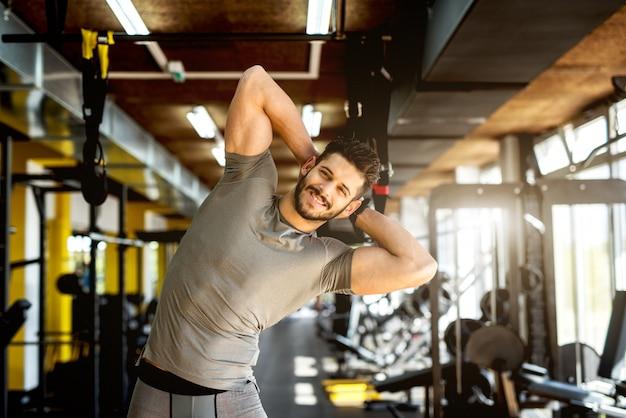 Uomo muscolare bello che allunga alla palestra.