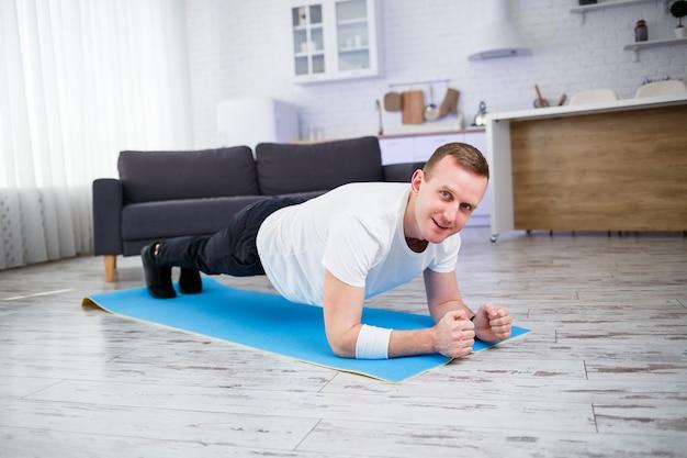 Bell'uomo muscoloso in una t-shirt che fa esercizi di plancia funzionali sul pavimento a casa. forma fisica a casa. uno stile di vita sano.