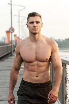 Bell'uomo muscoloso con il torso nudo durante l'allenamento fitness su un ponte