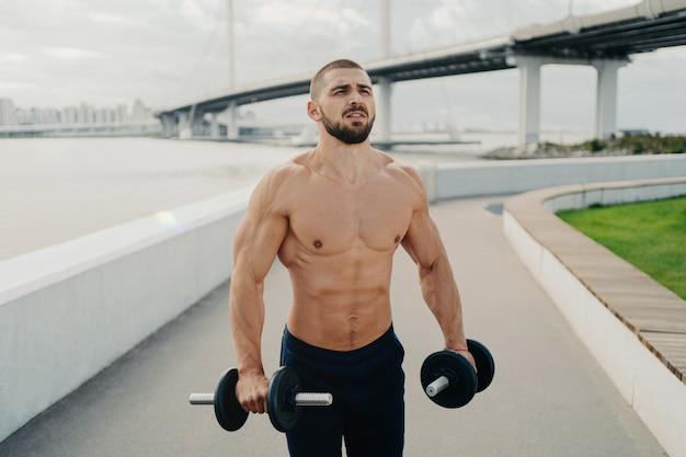 Bell'uomo muscoloso con il torso nudo all'aperto facendo allenamento fitness