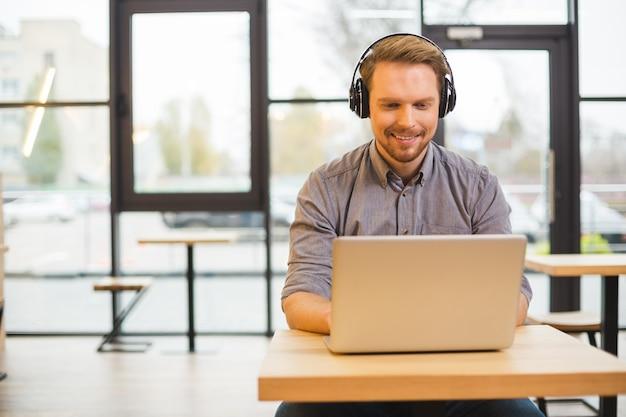 Bello bello allegro uomo seduto al computer portatile e indossa le cuffie mentre si lavora
