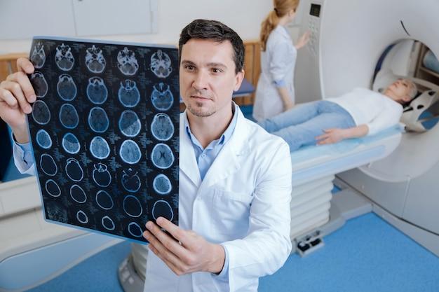 Oncologo maschio bello bello in piedi nel laboratorio medico e guardando le immagini di scansione mri mentre si esegue una scansione tomografica