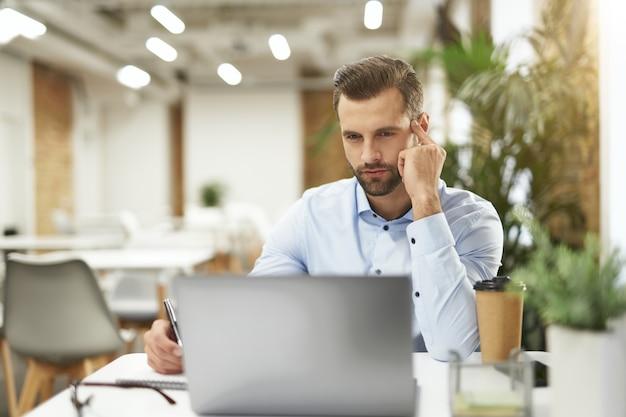 Bello impiegato d'ufficio al suo posto di lavoro con caffè e gadget
