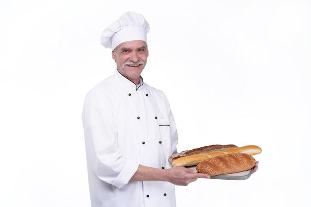 Bello vecchio fornaio in uniforme che tiene baguette con ripiani per pane sul muro bianco