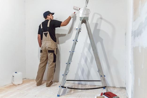 Bel pittore con rullo di vernice nella stanza vuota dipinge il muro