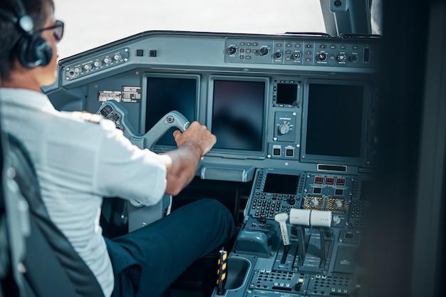 Il bel pilota con gli auricolari e gli occhiali è seduto nella cabina di pilotaggio e tiene il timone durante il decollo della macchina
