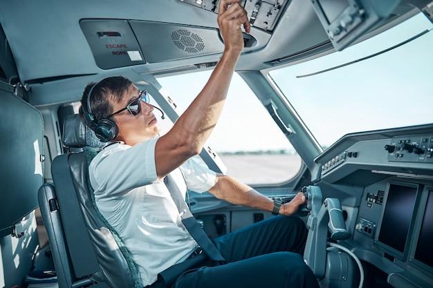 Il bel pilota con gli occhiali e gli auricolari è seduto all'interno dell'aereo al controllo e si sta preparando per la partenza