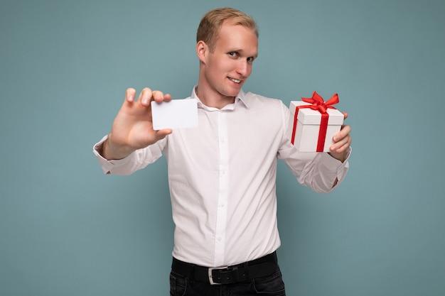 Bell'uomo biondo positivo che indossa una camicia bianca isolata su sfondo blu