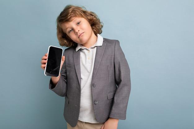 Bel ragazzo positivo con capelli ricci che indossa tuta tenendo il telefono isolato