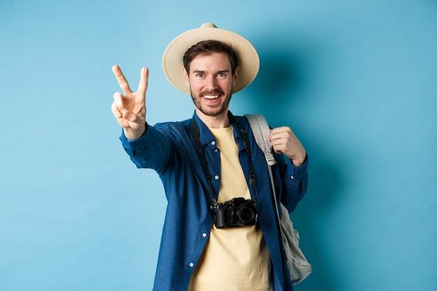 Turista bello ragazzo positivo che mostra il segno di pace sulle vacanze estive, godendo le vacanze tropicali sotto il sole, indossando il cappello di paglia, tenendo zaino e fotocamera, sfondo blu