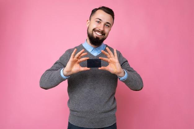 Bella persona di sesso maschile sorridente positiva che indossa abiti di tutti i giorni isolata sulla parete di fondo in possesso di carta di credito guardando la fotocamera