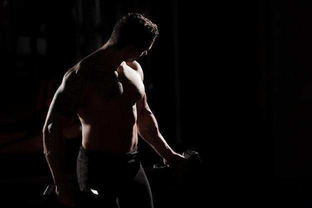 Culturista atletico del tipo di potere bello che fa gli esercizi con la testa di legno. concetto di corpo muscoloso fitness