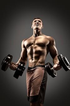 Culturista atletico bello dell'uomo di potere che fa gli esercizi con la testa di legno. corpo muscoloso fitness su sfondo scuro.