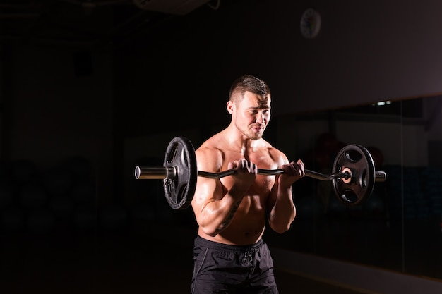 Uomo atletico bello potere con bilanciere. forte bodybuilder con six pack, addominali perfetti, spalle