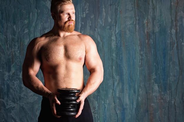 Uomo atletico bello potere con manubri su una parete scura.