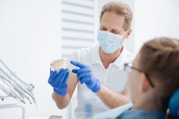 Medico addestrato preciso bello che spiega come bambina che necessitano di curare i suoi denti per essere sani