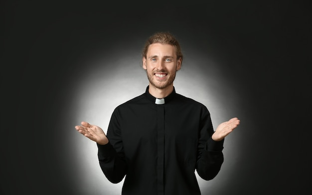 Bel sacerdote su sfondo scuro