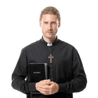 Bel prete con la bibbia su sfondo bianco
