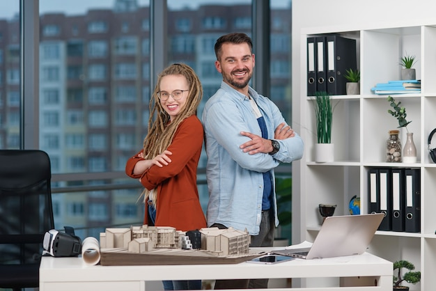 Il giovane ingegnere professionista bello sta schiena contro schiena con una collega graziosa con i dreadlocks all'ufficio di progettazione.