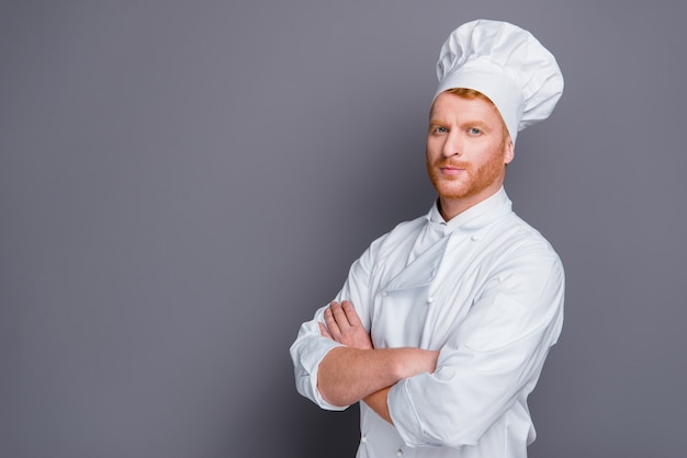 Chef redhead bello in posa contro il muro grigio