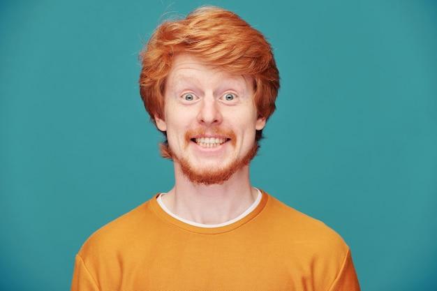 Bell'uomo dai capelli rossi con un maglione arancione che tiene il dito vicino alla bocca mentre chiede di mantenere la calma