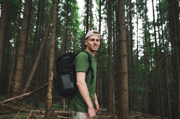 Viaggiatore maschio incurante rilassato bello che posa sulla macchina fotografica al bosco