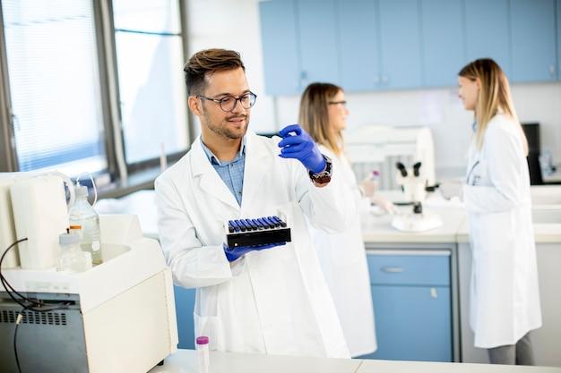Bello ricercatore in indumenti da lavoro protettivi in piedi in laboratorio e analizzando campioni di liquidi