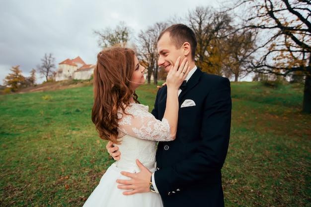 Sposo romantico bello che bacia bella sposa castana sul loro giorno delle nozze felice sul territorio del palazzo