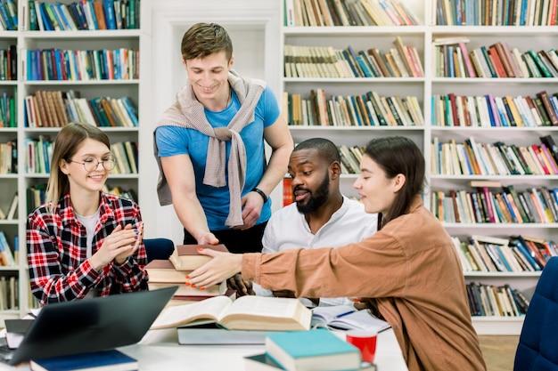Studente soddisfatto bello del giovane che mette molti libri differenti sul tavolo per i suoi multi amici razziali dell'università, sedentesi e che studiano insieme nella sala di lettura delle biblioteche.