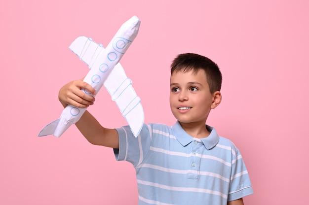 Scolaro bello che gioca con un aeroplano di carta su sfondo rosa con spazio di copia.