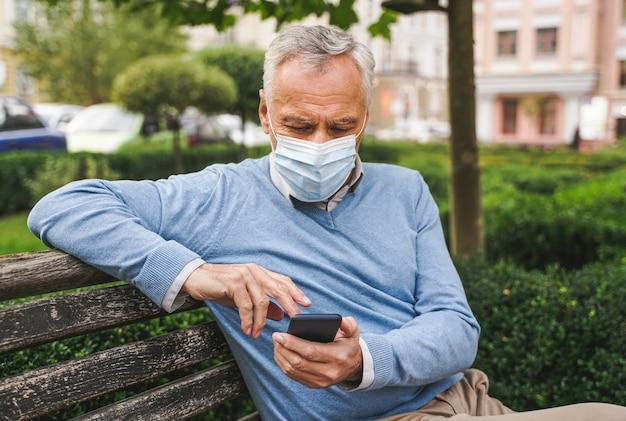 Bello senior adulto con maschera facciale in un parco durante la pandemia del coronavirus