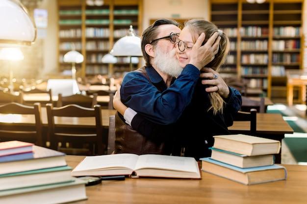 Nonno barbuto senior bello che abbraccia e bacia la sua nipote carina, bambina in occhiali, seduto al tavolo con molti libri nella biblioteca antica