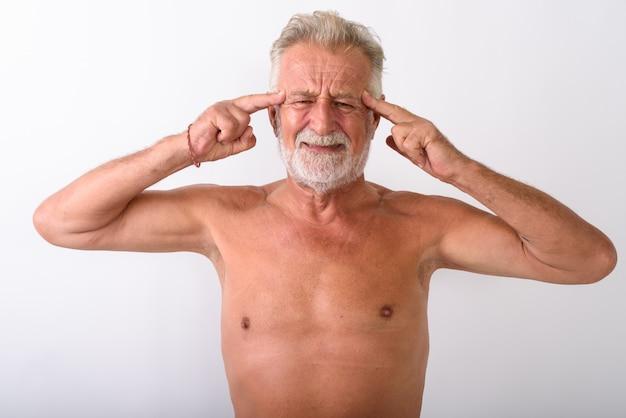 Uomo barbuto anziano bello che ha torso nudo di emicrania su bianco
