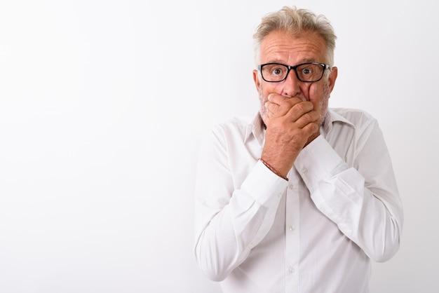 Bell'uomo barbuto anziano che sembra scioccato mentre copre la bocca e indossa occhiali da vista su bianco