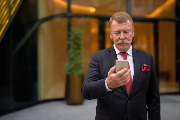 Handsome senior imprenditore con i baffi utilizzando il telefono in città