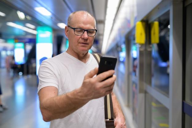 Uomo turistico senior bello che utilizza il telefono per le indicazioni alla stazione ferroviaria