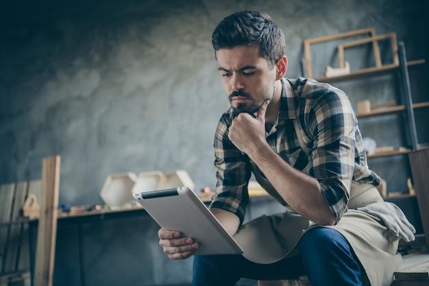 Un bel ragazzo serio che tiene il sito web di e-reader che controlla gli ordini online della posta elettronica pensa a come migliorare il servizio del negozio di falegnameria del proprietario del settore dell'industria del legno al chiuso