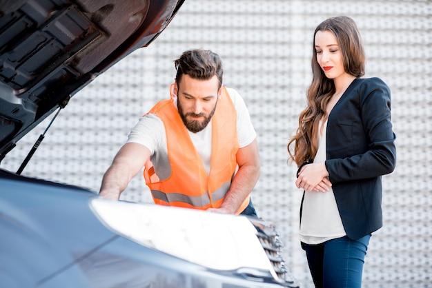 Un bell'operatore di servizio che consulta o fornisce assistenza tecnica dell'auto rotta alla donna d'affari in piedi vicino all'edificio del centro servizi