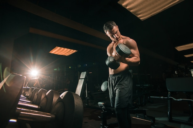 Bel ragazzo torso nudo sollevamento pesi pesanti mentre è seduto sulla panchina in palestra buia