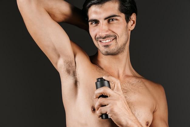 Bell'uomo a torso nudo in piedi isolato, spruzzando deodorante sulla sua ascella
