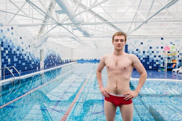 Bell'uomo senza camicia in piedi con le mani sui fianchi in piscina