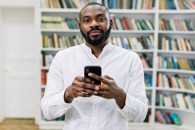 Studente maschio o uomo d'affari afroamericano astuto bello in camicia bianca che scrive un messaggio o un email sul suo telefono cellulare mentre stando nella biblioteca moderna