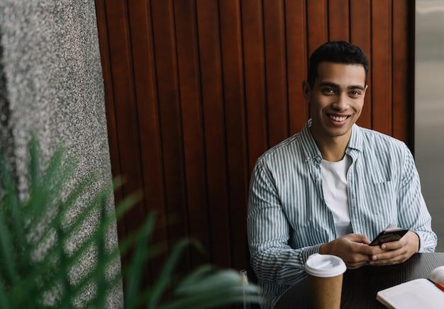 Uomo afroamericano sorridente bello che per mezzo del telefono cellulare, comunicazione, prenotando online