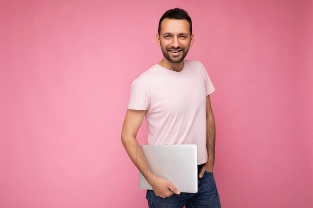 Bello sorridente brunet uomo che tiene il computer portatile che guarda l'obbiettivo in t-shirt su sfondo rosa isolato.