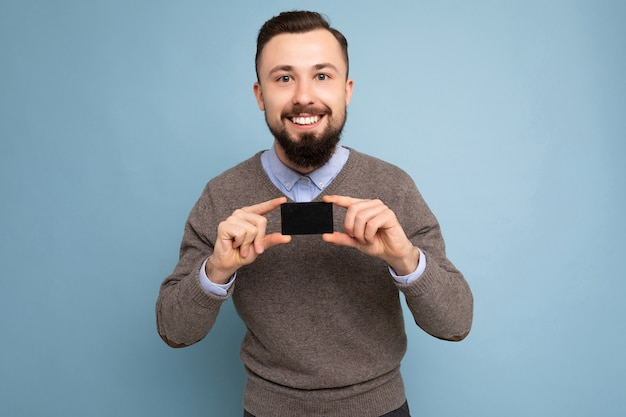 Uomo barbuto castana sorridente bello che porta maglione grigio e camicia blu isolato sulla carta di credito della tenuta della parete del fondo che guarda l'obbiettivo.