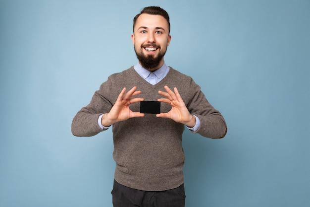Bello sorridente bruna uomo barbuto che indossa un maglione grigio e una camicia blu isolata sulla parete di fondo che tiene la carta di credito che guarda l'obbiettivo.