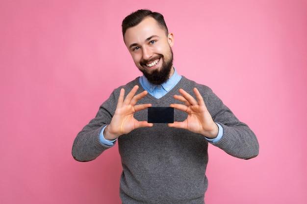 Bello sorridente brunetta uomo barbuto che indossa un maglione grigio e camicia blu isolato
