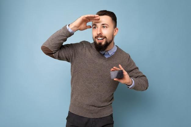 Bello sorridente uomo barbuto brunetta che indossa un maglione grigio e una camicia blu