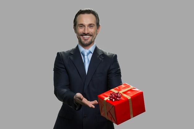 Uomo d'affari sorridente bello che mostra confezione regalo. uomo felice in giacca e cravatta che offre casella attuale. bellissimo regalo per te.